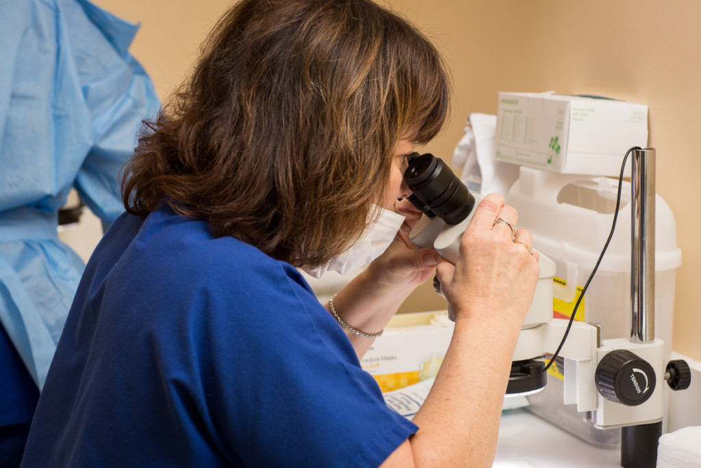 A staff member looking into a microscope for a hair restoration procedure at DiStefano Hair Restoration Center in Worcester, MA